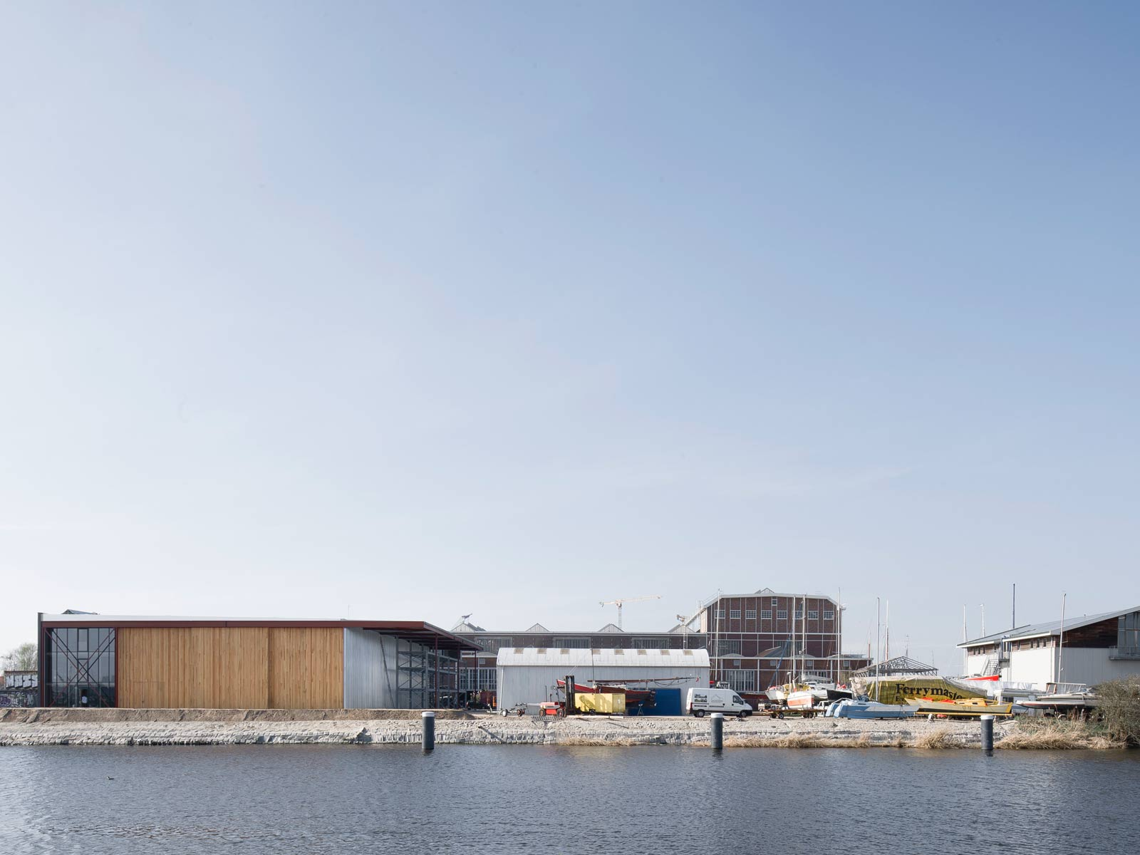 exterior photo across Zijkanaal I showing boat hangar along the quay and NDSM shipbuilding warehouse in the back