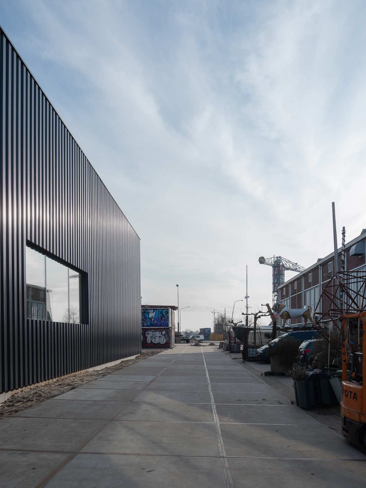 exterior photo showing reflections in rectangular window in currogated steel cladding