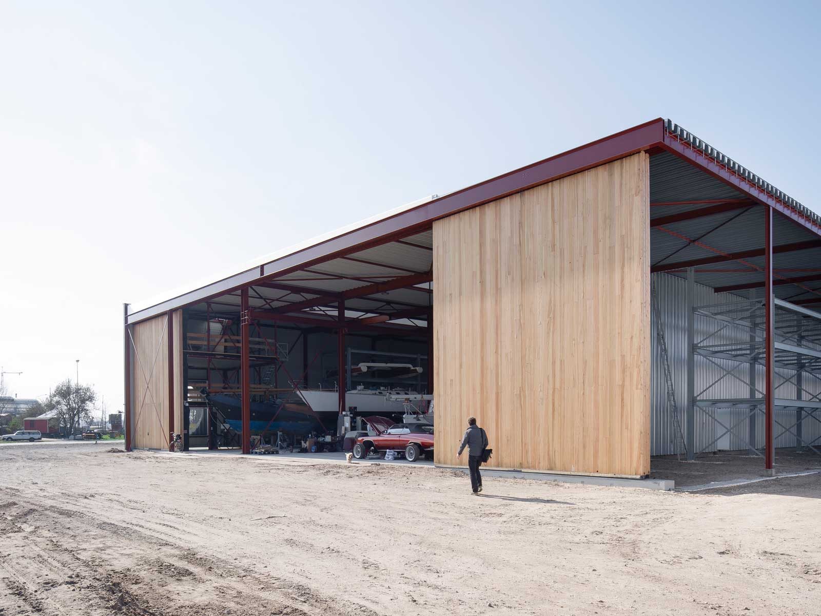 exterior photo showing timber sliding hangar doors fully open with boats inside