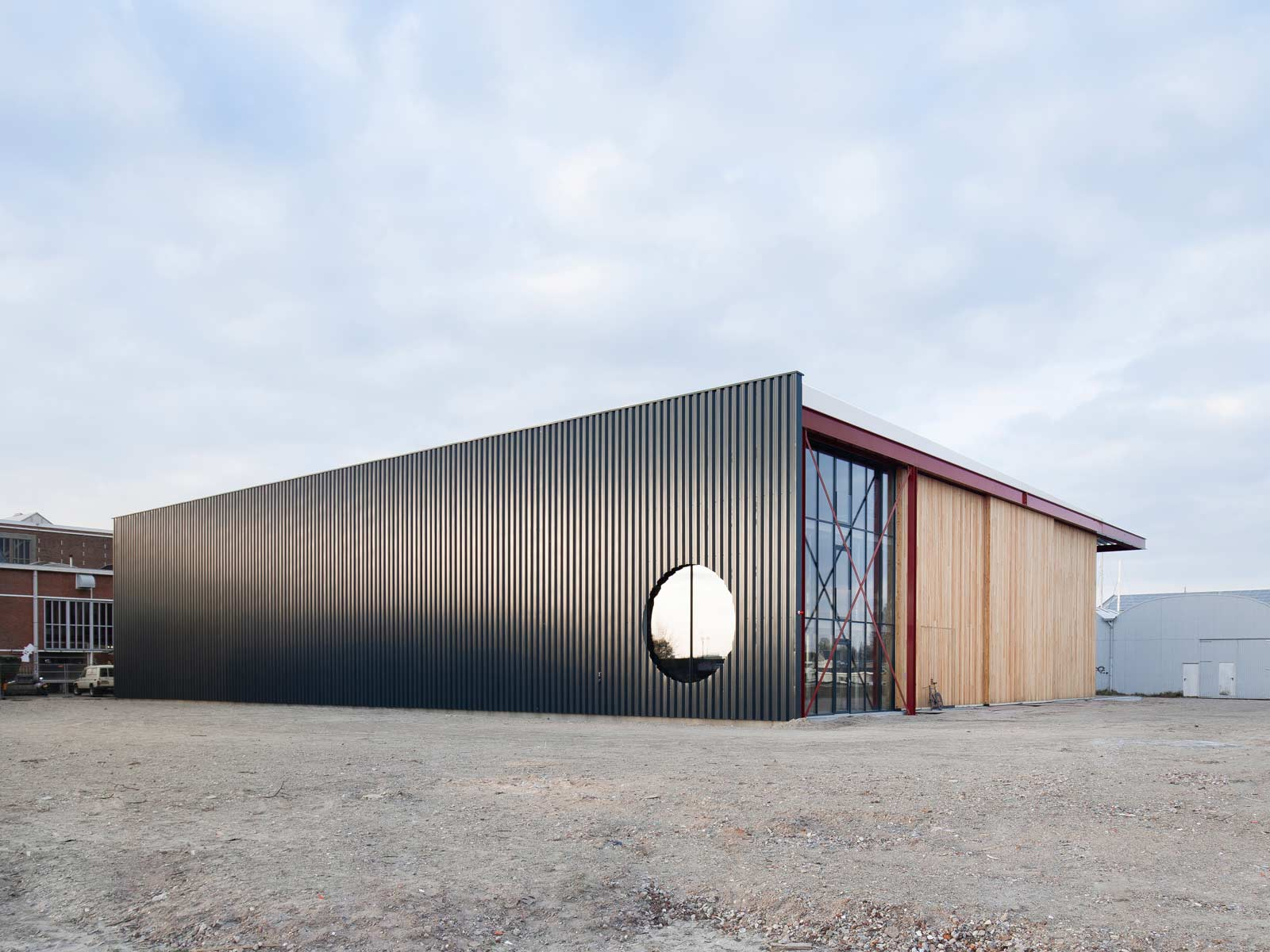 exterior photo with evening light showing facade with circular window in steel cladding by BETA architects Evert Klinkenberg Auguste Gus van Oppen