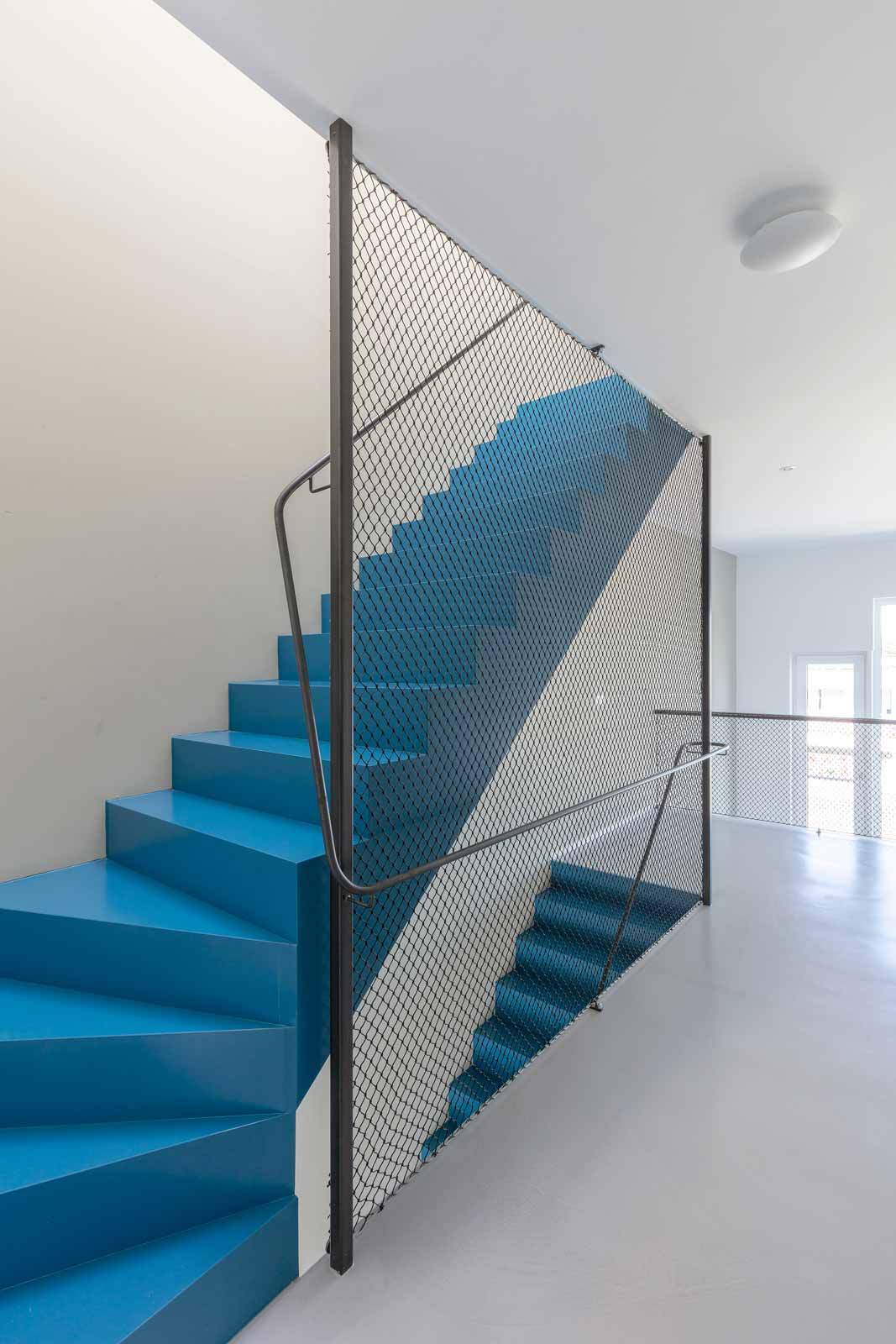 blue house by BETA interior photo stacked staircases with steel railing