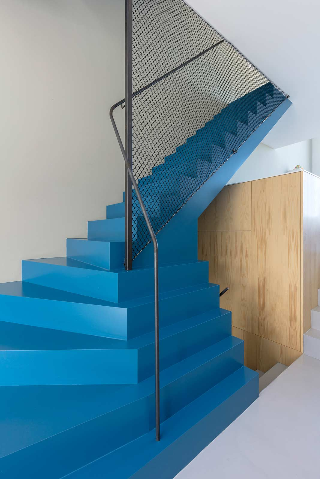 blue house by BETA interior photo sculptural staircase with steel railing