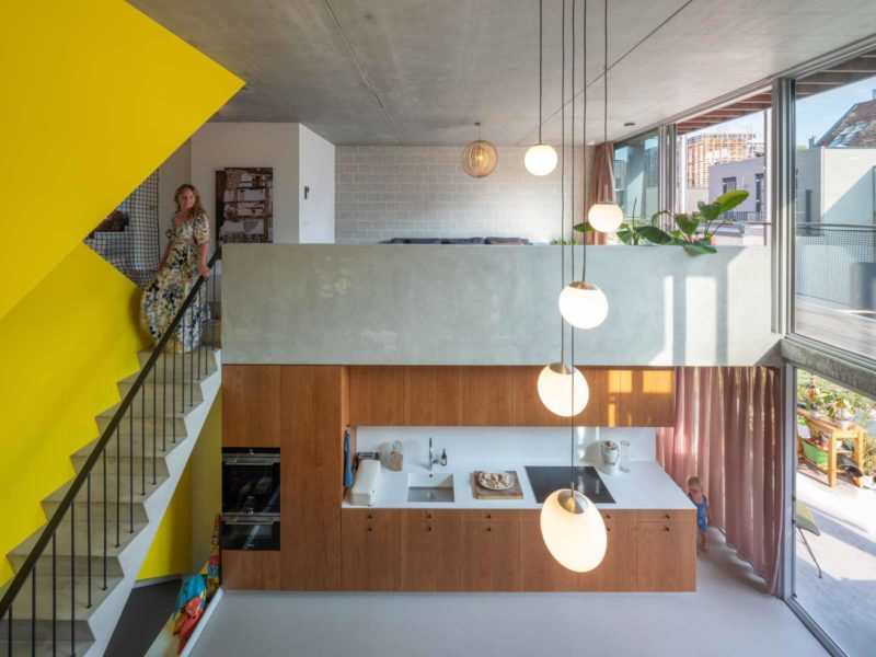 three generation house by BETA photo interior kitchen and living room void with yellow staircase by Ossip