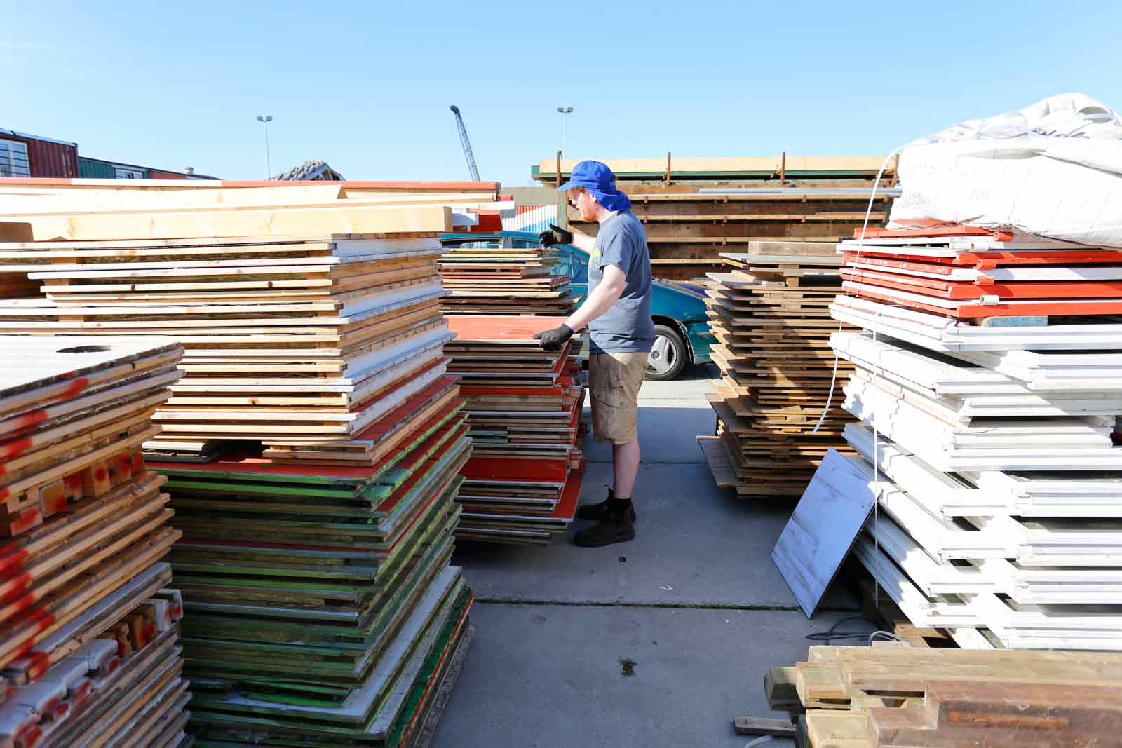 photograph of a builder with a blue hat on standing next to stacks of reclaimed wood for Treehouse NDSM