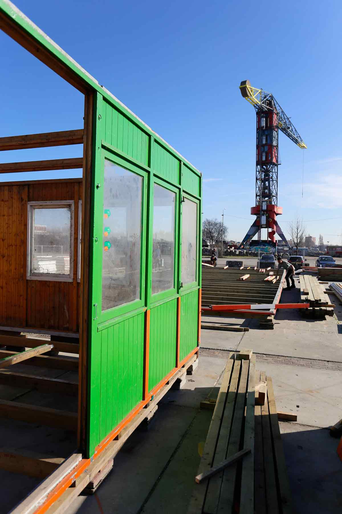 photograph of a green shack under construction to the left and the NDSM crane in the background